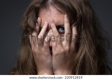 Frightened girl in water droplets on grey background - stock photo
