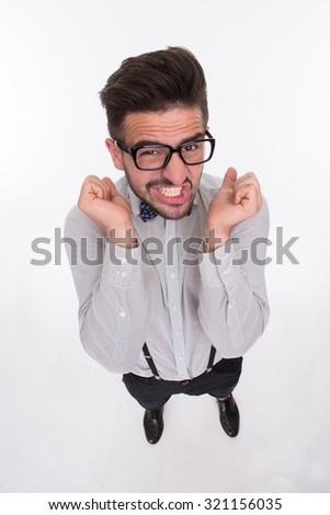 Frightened hipster man isolated on white background. Short-haired man in glasses keeping his arms in front of him in studio. - stock photo