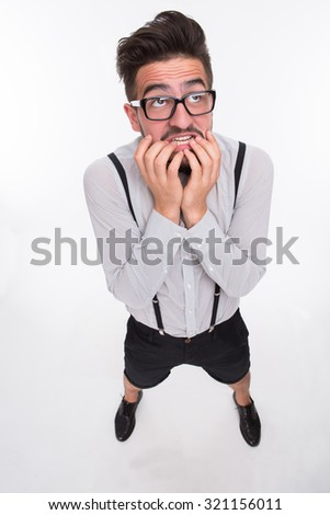Frightened hipster man shaking in shoes in photo studio. Hnadsome man keeping fingers near his mouth isolated on white background. - stock photo