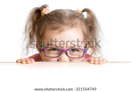 frightened kid in spectacles looking from under table desk  - stock photo