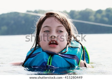 Frightened little girl in a lake wearing a life jacket. - stock photo