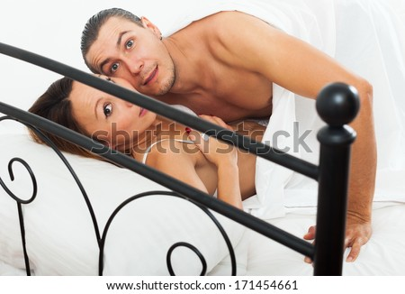 Frightened lovers caught during adultery in bed - stock photo