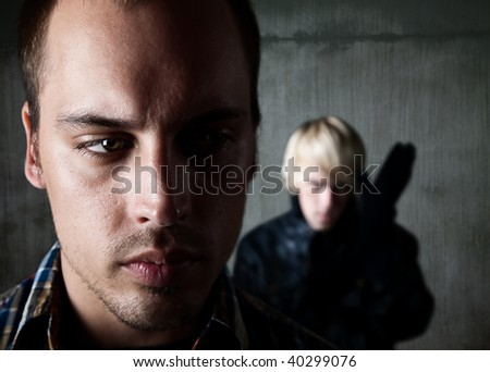 Frightened man being followed by young male criminal - stock photo