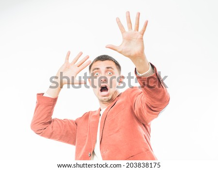 Frightened man holding his hands up - stock photo