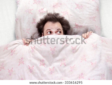 frightened man lying in bed - stock photo