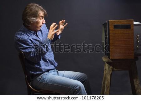 frightened man watching TV. - stock photo