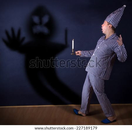 frightened man with candle in pajamas  - stock photo