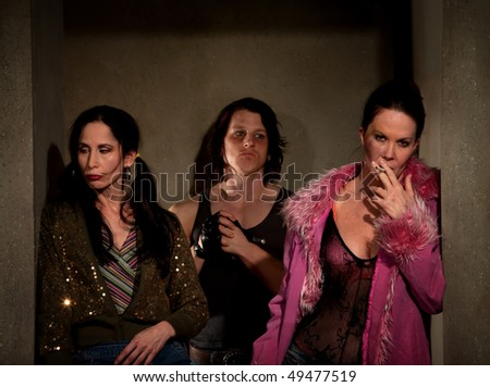 Frightened prostitutes in hallway with pimp - stock photo