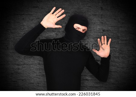 frightened robber raised his hands up on gray background - stock photo