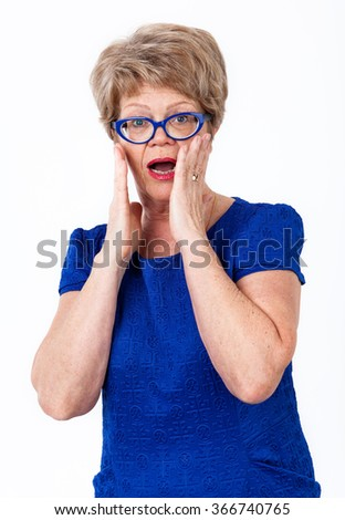 Frightened senior woman standing with wide opened eyes and mouth, white background