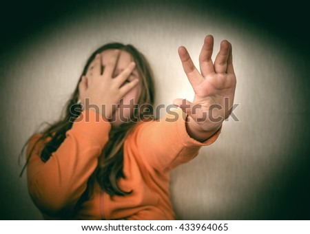 Frightened Teenage Girl Making Stop Gesture. Selective focus on hand - stock photo