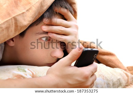 Frightened Teenager with Cellphone under Blanket at the Home - stock photo