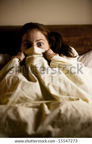 Frightened Woman in Bed with the Sheets Pulled Up to her Face - stock photo