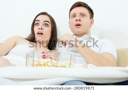 Frightened young attractive couple sitting on the couch in living room at home covered with blanket and watch scary horror on television with popcorn. Terrified man and woman watching violent movie - stock photo
