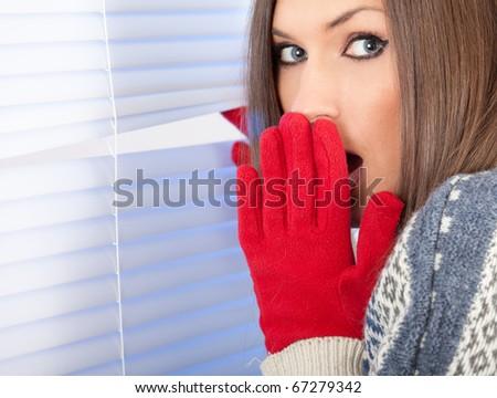 frightened young beautiful woman is waiting near window - stock photo