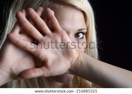 frightened young blond woman showing stop with two hands - stock photo