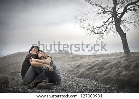 frightened young couple sitting in the middle of nature embrace - stock photo