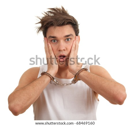 frightened young handsome man with handcuffed hands - stock photo