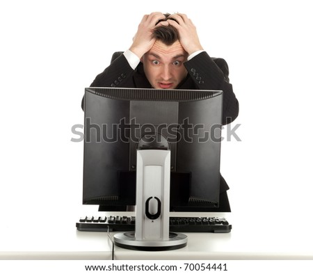 frightened young man in black suit working on computer - stock photo