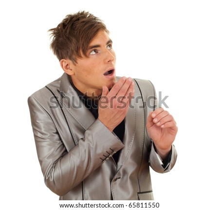 frightened young man in grey suit with hand near face - stock photo