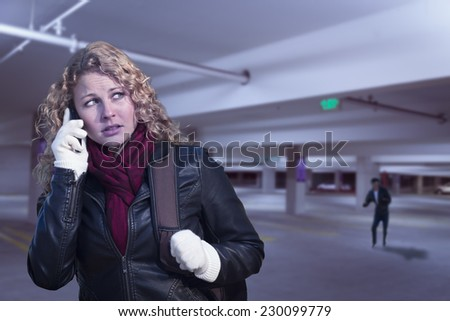 Frightened Young Woman On Cell Phone As Dark Man Lurks in Parking Structure. - stock photo