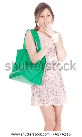 frightened young woman with green ecological shopping bag checking purchases list - stock photo
