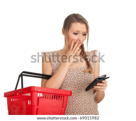 frightened young woman with red basket checking purchases list - stock photo