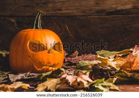 Frightening Halloween pumpkin on leaves - stock photo