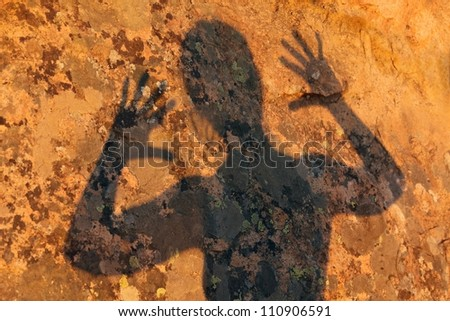 frightening human shadow gesture on granite rock - stock photo