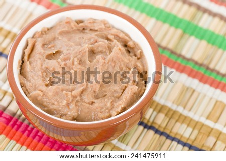 Frijoles Refritos - Bowl of Mexican refried beans on a colourful background.  - stock photo