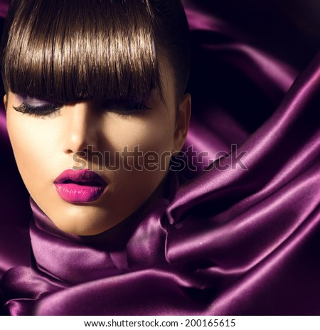 Fringe. Fashion Model Girl With Trendy Hairstyle. Haircut. Stylish Beauty Brunette Woman on violet silk fabric. Beautiful Make up. Vogue Style. Hair cut