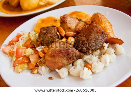 Fritada, fried pork, typical ecuadorian dish served with hominy, sweet plantain and potato tortillas - stock photo
