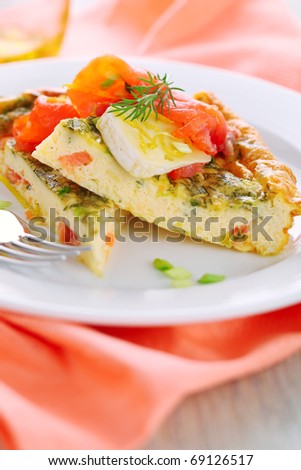 Frittata with salmon and camembert on white plate - stock photo