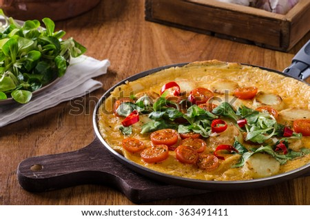 Frittata with tomatoes, herbs and chilli, little lettuce inside, very simple but delicious food - stock photo