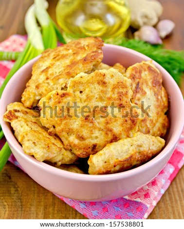 Fritters minced chicken in a pink bowl, napkin, oil, dill, garlic, ginger, green onions on a wooden board