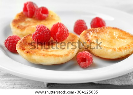 Fritters of cottage cheese with raspberries in plate on table, closeup