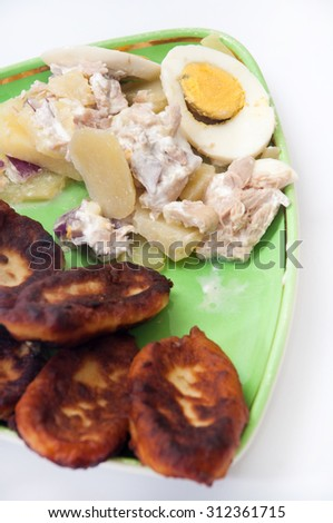 Fritters of potatoes with potato salad and boiled eggs. - stock photo