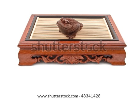 frog figurine on chinese wooden table isolated on white