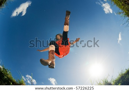Frog perspective shot of a jumping young woman - stock photo