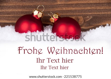 Frohe Weihnachten, german Christmas Greetings which means Merry Christmas, in the Snow with red Christmas Balls and Space for your Text - stock photo