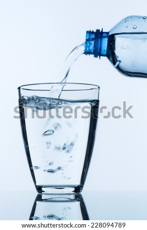 from a bottle of water being poured into a glass, symbol photo for drinking water needs and consumption - stock photo