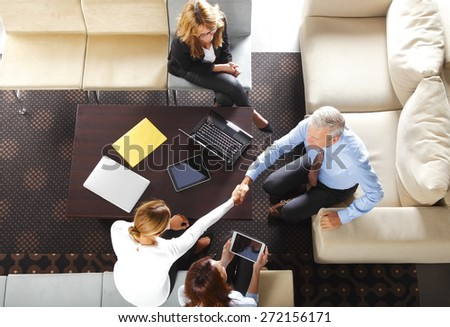 From above image of business people make a deal and shaking hands while sitting at meeting.  - stock photo