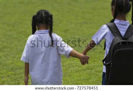 From behind Thai student hand in hand with dear friends before school in soccer field. Education is essential for children. Go to study.