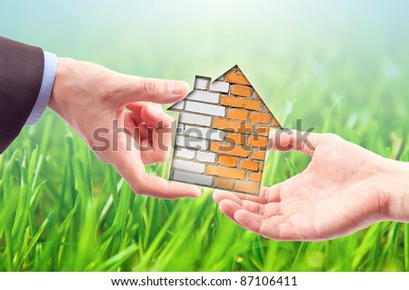 From hand to hand the house as a symbol of real estate business - stock photo