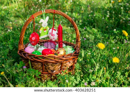 From left on the lawn Easter wicker basket decorated with painted eggs and felt bunny, right empty space on background of grass and yellow flowers. Easter basket, felt bunny, empty space. Horizontal.