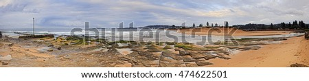 From rock pool to long clean Collaroy beach behind Narrabeen lake ocean entrance point in wide panorama at sunrise. Seascape of Northern beaches in Sydney.