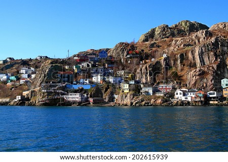 From the Atlantic Ocean level View over Newfoundland Capital St.Johns Houses on East end which are reaching the foot steps of million years old rock of Signal Hill  - stock photo