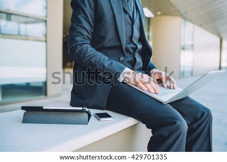 From the neck down view of middle age caucasian businessman using technological devices like notebook leaning on his knee, smart phone and tablet - business, work, multitasking concept - stock photo