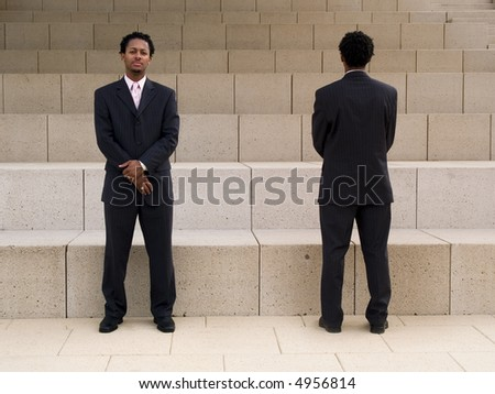 Front and back of a buisnessman on steps in front of a modern building.