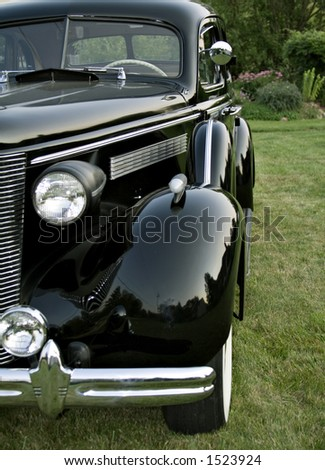 Front and Driver's side view of black vintage Buick Sedan - 1930's.  Garden background. - stock photo